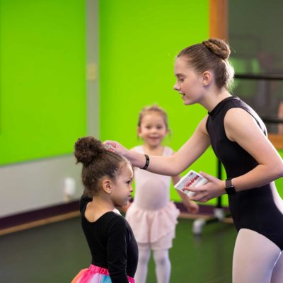 Older Dancer helping a Younger Dancer